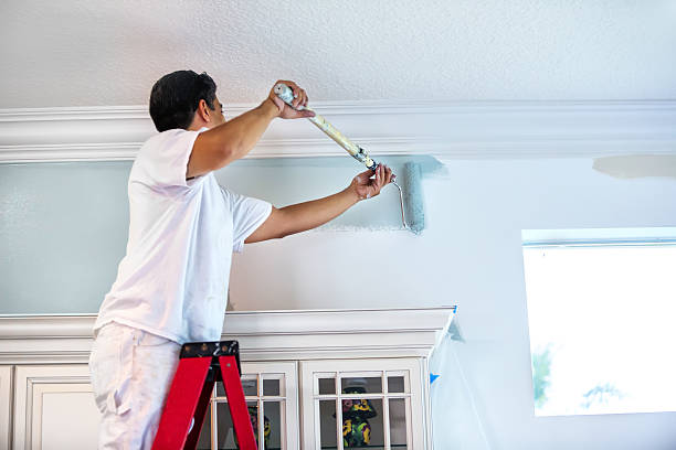 A housepainter stands on a ladder to paint the walls inside a residential home.